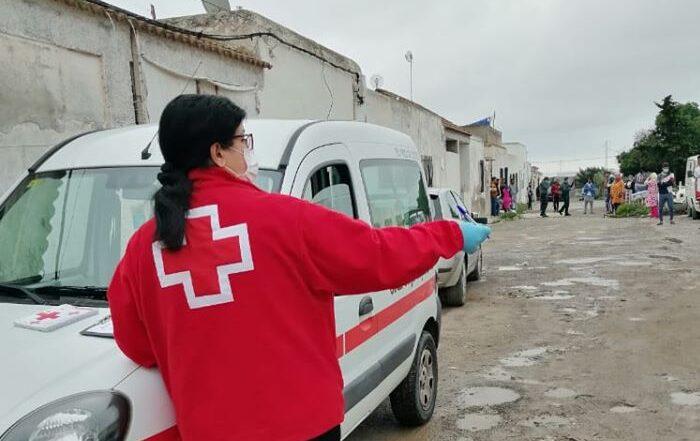 Voluntaria de Cruz Roja visita un asentamiento de personas migrantes.