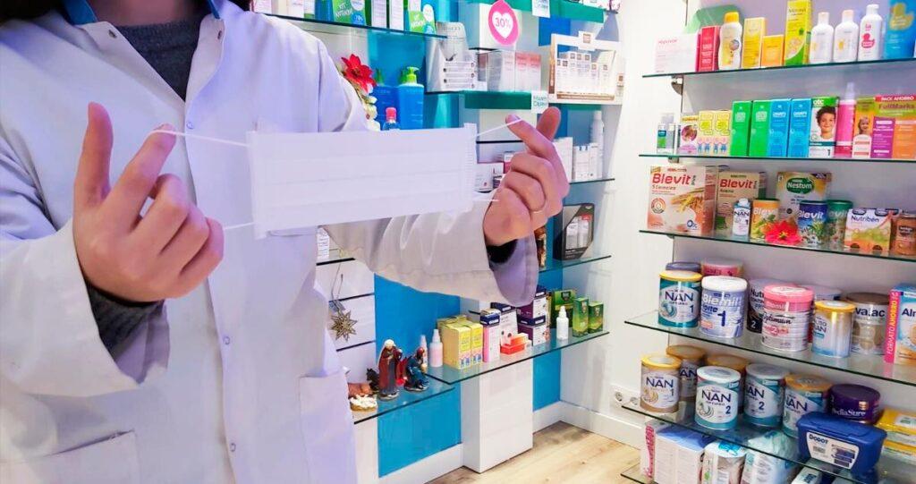 Profesional de farmacia manipulando una mascarilla