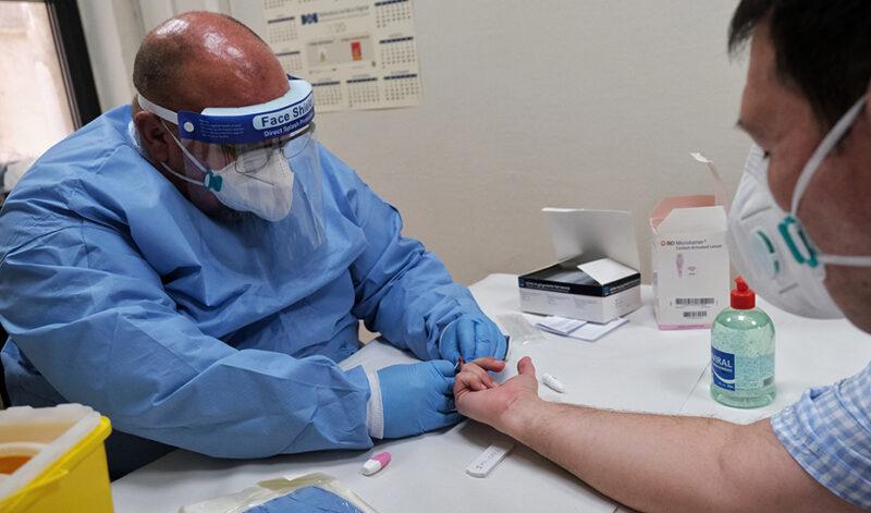 Un sanitario recoge muestras de sangre de un paciente
