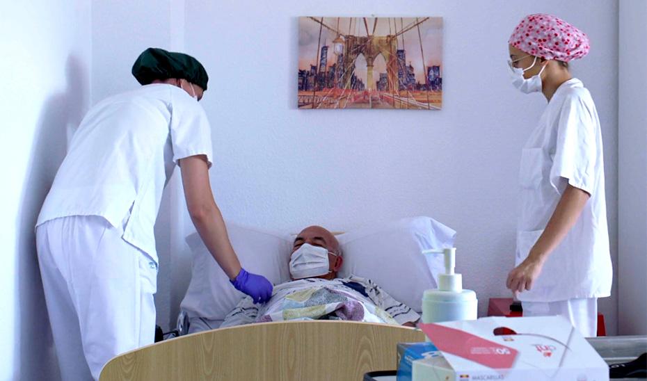 Dos trabajadoras de una residencia de mayores medicalizada atienden a una persona enferma.