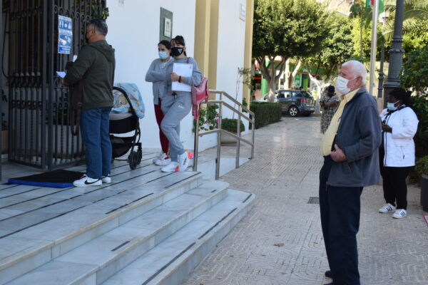 Vecinos y vecinas de Vícar guardan cola en la puerta del Ayuntamiento