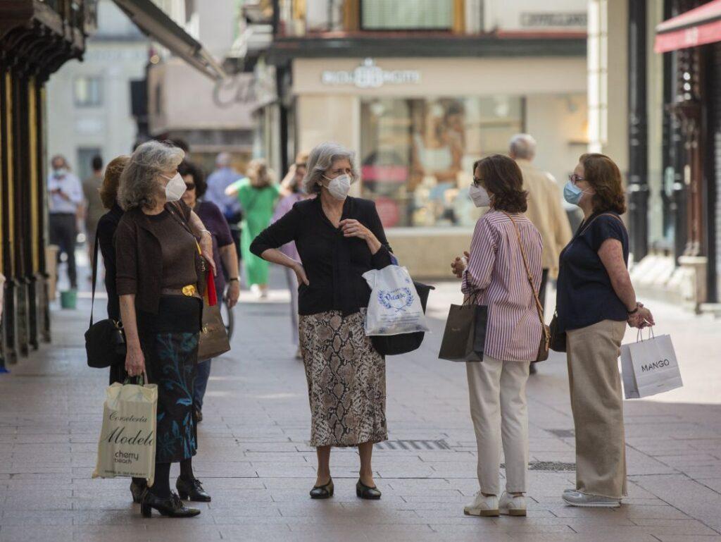 Grupo de mujeres en la vía pública con mascarillas
